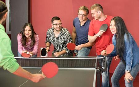 Photo for Group of happy young friends playing ping pong table tennis - Fun moment in game room of traveler youth hostel - Concept of vintage sport and genuine emotions - Main focus on two guys with eye glasses - Royalty Free Image