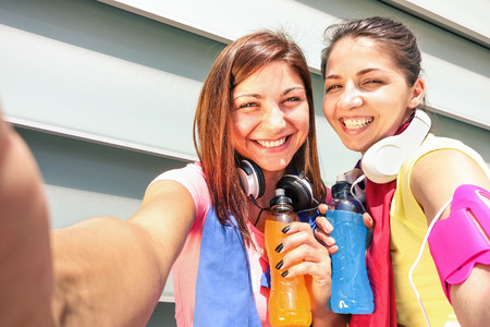 Photo for Sporty girlfriends taking selfie during a break at run training in urban area - Sport Young happy women having fun together with fitness jogging workout - Fashion sport clothes and energetic drinks - Royalty Free Image