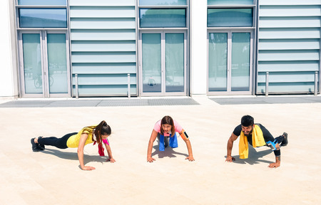 Group of young people performing pushups in modern urban area - Fitness girls exercising with male trainer coach in the city - Sport concept with friends practicing together in a sunny bright day
