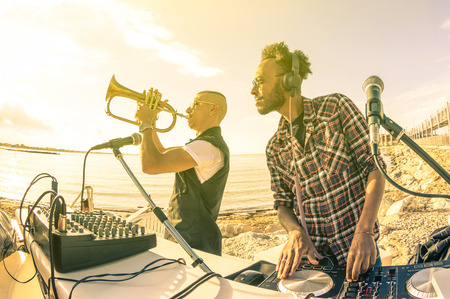 Photo pour Trendy hipster dj playing summer hits at sunset beach party with trumpet jazz performer  Holidays vacation concept at open air club with house music groove location  Warm vintage sunshine filter - image libre de droit