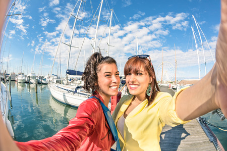 Young women girlfriends taking a selfie at harbour docks with sailboats