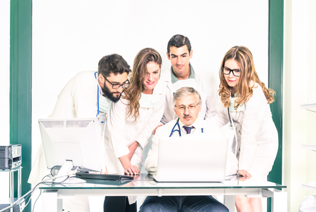 Photo pour Group of young medicine students with senior doctor at health care clinic - University college medical apprentices learning together with teacher at computer - Hospital studio and healthcare people - image libre de droit