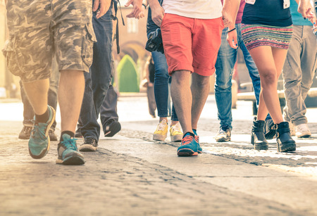 Crowd of people walking on the street - Detail of legs and shoes moving on sidewalk in city center - Travellers with multicolor clothes on vintage filter - Shallow depth of field with sunflare halo