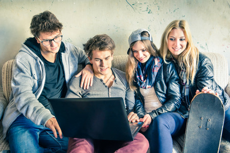 Group of young hipster best friends with computer in urban alternative studio - Concept of friendship and fun with new trends and technology - Vintage filtered look with soft focus on guy with laptopの写真素材