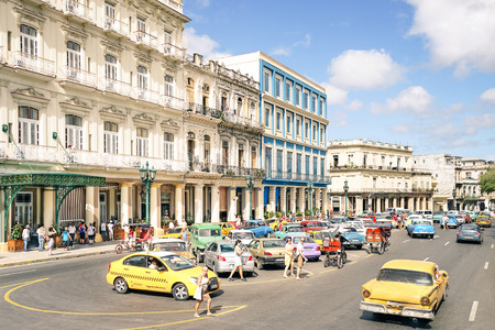 HAVANA, CUBA - NOVEMBER 17, 2015: everyday life with tourists and local people in front of the Galician Palace on Prado Street at the beginning of   Paseo de Marti  - Warm afternoon color tones