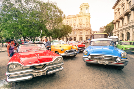 Photo pour HAVANA, CUBA - NOVEMBER 17, 2015: multicolored vintage american cars in Havana City with National Museum of Fine Arts - Warm afternoon color tones with sunshine halo - image libre de droit