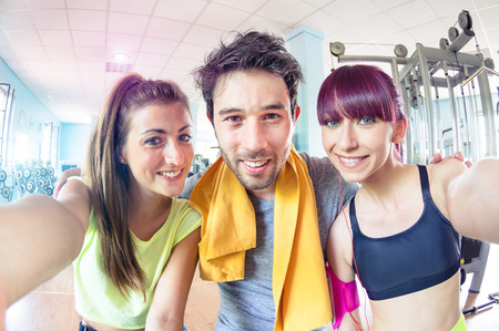 Photo for Happy active friends trio taking selfie in gym training studio center - Sporty people ready for fitness time - Healthy lifestyle and sport concept - Soft bright cyan marsala desaturated filtered look - Royalty Free Image