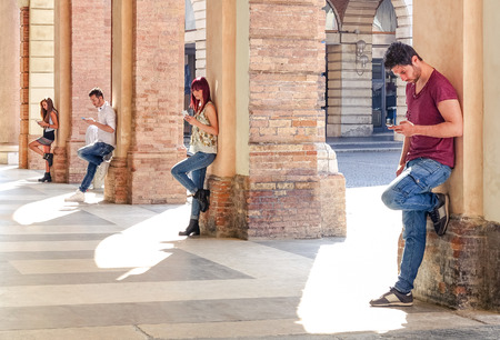Photo pour Group of young fashion friends using smartphone in urban old city center - Technology addiction in actual lifestyle with mutual disinterest towards each other - Addicted people to modern mobile phones - image libre de droit