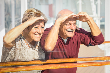 Foto de Happy senior couple having fun looking to future - Concept of active playful elderly during retirement - Travel lifestyle with childish funny attitude - Marsala color tone with soft glass reflections - Imagen libre de derechos
