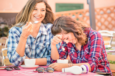 Happy couple of girlfriends drinking cappuccino and laughing together - Happiness concept with young women talking and having fun at coffee bar - Warm vintage filter with focus on girl face at right