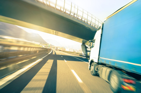 Foto de Generic semi truck speeding on highway under overpass - Transport industry logistic concept with semitruck container driving fast on speedway - Soft vintage filter with sunshine halo and blurred edges - Imagen libre de derechos