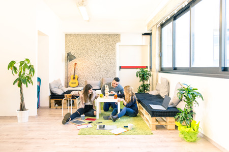 Photo for Group of young people employee workers having a break in start up office - Business concept of human resource and fun on working time - Start up entrepreneurs playing wood game - Bright vintage filter - Royalty Free Image