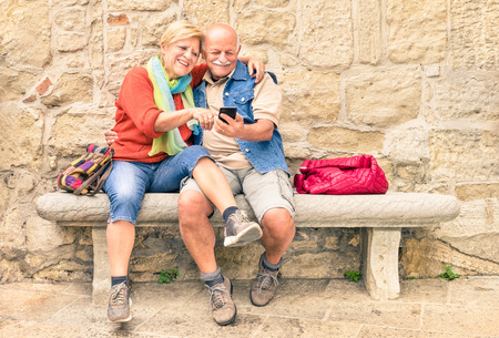 Photo pour Happy senior couple having fun together with mobile smart phone - Concept of active playful elderly during retirement - Travel lifestyle concept with retired people - Warm cloudy afternoon color tones - image libre de droit