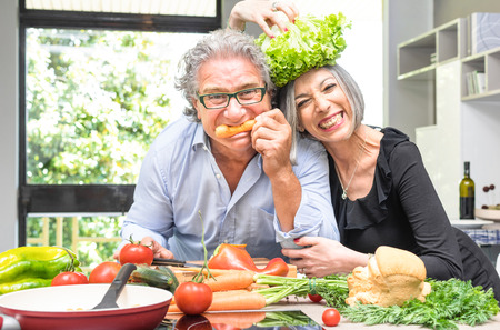 Foto de Senior couple having fun in kitchen with healthy food - Retired people cooking meal at home with man and woman preparing lunch with bio vegetables - Happy elderly concept with mature funny pensioner - Imagen libre de derechos