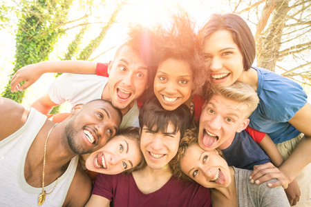 Foto de Best friends taking selfie outdoor with back lighting - Happy youth concept with young people having fun together - Cheer and friendship against racism - Vintage marsala filter and sunshine halo flare - Imagen libre de derechos
