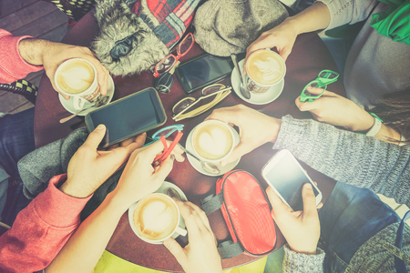 Group of friends drinking cappuccino at coffee bar restaurant - People hands using smartphone on upper point of view - Technology concept with addicted men and women - Lomo vintage filter with halo