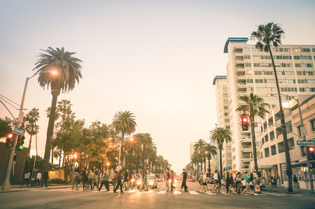 Photo for Locals and tourists walking on zebra crossing and on Ocean Ave in Santa Monica after sunset - Crowded streets of Los Angeles and California state - Warm desat twilight color tones with blurred people - Royalty Free Image