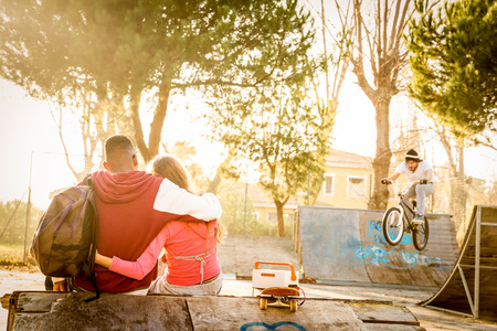 Multiracial couple in love sitting at skate park with music watching friends on bmx freestyle exhibition - Urban relationship concept with young people having fun outdoors - Warm contrasted filter