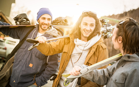 Best friends having fun together walking with ski and snowboard at mountain trip - Friendship concept with young people hangout loving winter sports travel - Warm filter with backlight sunshine halo