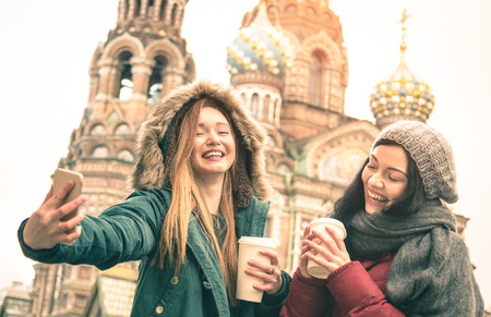Happy girlfriends taking winter selfie at  Savior on Spilled Blood  church in Saint Petersburg - Friendship concept with girls having fun together drinking coffee outdoor - Focus on left young woman