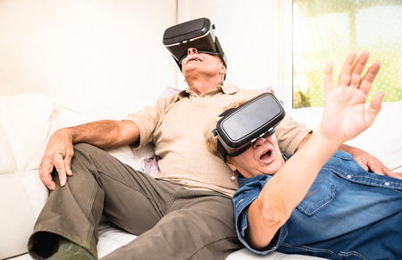 Photo pour Senior couple having fun together with virtual reality headset - Retired people using new vr goggles glasses - New trends and technology concept - Focus on mature woman - Neutral apartment lights - image libre de droit