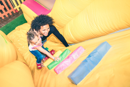 Photo pour Latin american dad playing with mixed race daughter on inflatable slide at kindergarten playroom - Family concept with happy multiracial child and father having fun together at kids playground toyroom - image libre de droit