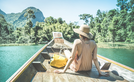 Photo pour Young woman traveler on longtail boat trip at island hopping in Cheow Lan Lake - Wanderlust and travel concept with adventure girl tourist wanderer on excursion in Thailand - Retro turquoise filter - image libre de droit