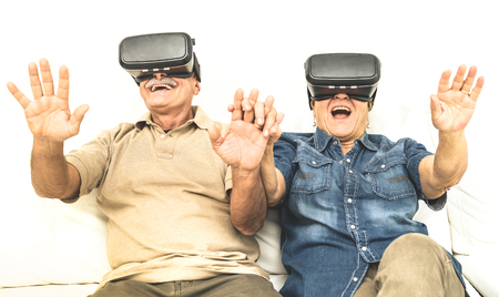 Foto de Senior mature couple having fun together with virtual reality headset sitting on sofa - Happy retired people using modern vr goggle glasses - New trends and technology concept and funny active elderly - Imagen libre de derechos