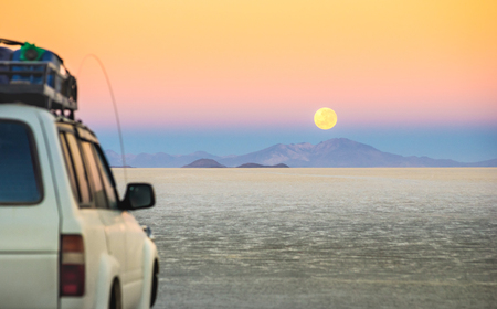 Full moon sunset with off road jeep vehicle on Salar De Uyuni - World famous nature wonder place in Bolivia - Travel and wanderlust concept in South American exclusive landscape - Focus on infinity