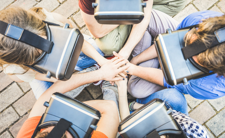 Photo pour Top view of friends group playing on vr glasses with hands stacking - Virtual reality and wearable tech concept with young people having fun together with headset goggles - Digital generation trends - image libre de droit
