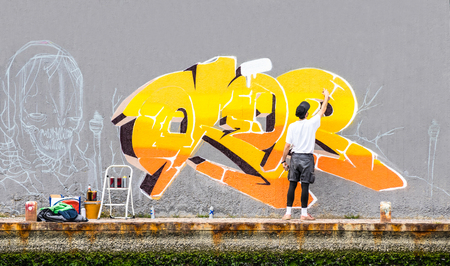 Foto de Street artist painting colored graffiti on public space wall - Modern art concept of urban guy performing and preparing live murales paint with yellow aerosol color spray - Cloudy afternoon filter - Imagen libre de derechos