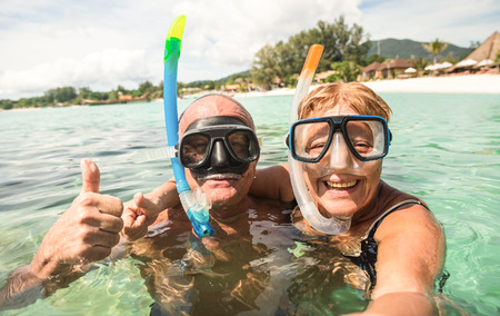 Foto de Senior happy couple taking selfie in tropical sea excursion with water camera - Boat trip snorkeling in exotic scenarios - Active retired elderly and fun concept around the world - Warm bright filter - Imagen libre de derechos