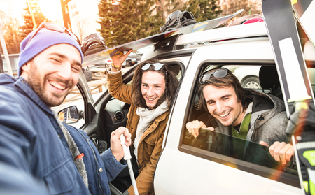 Best friends having fun taking selfie at car for ski and snowboard on mountain trip - Friendship hangout concept with young people loving winter sports travel - Vintage desaturated contrast filter