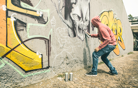 Foto de Street artist painting colorful graffiti on generic wall - Modern art concept with urban guy performing and preparing live murales with multi color aerosol spray - Contrast retro vintage filter - Imagen libre de derechos