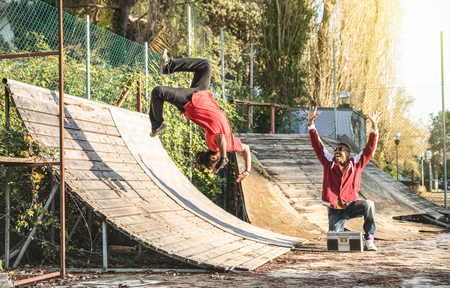Urban athlete breakdancer performing somersault jump flip at skate park - Afroamerican guy watching friend acrobat dancing with extreme flipping move - Breakdance acrobatic and friendship concept