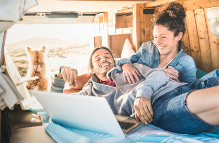 Hipster couple with dog traveling together on retro mini van transport - Life inspiration concept with indie people on minivan adventure trip watching laptop pc in relax moment - Warm vintage filter