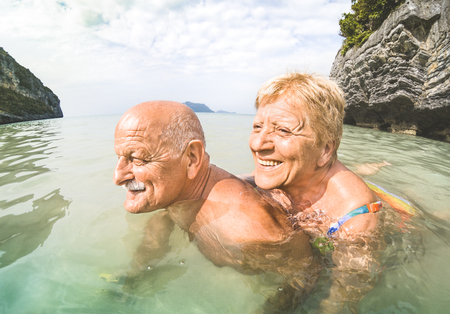 Photo pour Senior couple vacationer having genuine playful fun on tropical beach in Thailand - Snorkel tour in exotic scenario - Active elderly and travel concept around the world - Warm afternoon bright filter - image libre de droit