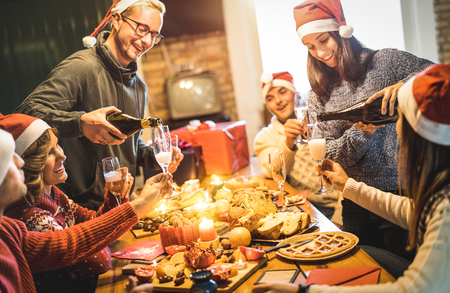Photo pour Friends group with santa hats celebrating Christmas with champagne and sweets food at home dinner - Winter holidays concept with people enjoying time and having fun eating together - Warm filter - image libre de droit