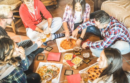 Photo pour Happy friends eating take away pizza at home after work - Friendship concept with young people enjoying time together and having genuine fun in start up office - Focus on beers and french fries - image libre de droit