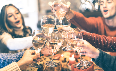 Foto de Friends group celebrating Christmas toasting champagne wine at home dinner - Winter holiday concept with young people enjoying time and having fun together - Azure vintage filter with focus on glasses - Imagen libre de derechos