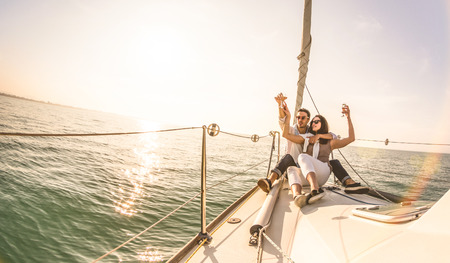 Photo pour Young lovers couple on sail boat with champagne at sunset - Exclusive luxury concept with rich millennial people lifestyle on tour around the world - Soft backlight focus on warm sunshine filter - image libre de droit