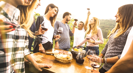 Foto de Millenial friends having fun time drinking red wine oudoors - Happy fancy people enjoying harvest at farmhouse vineyard winery - Youth friendship concept together at pic nic garden party - Warm filter - Imagen libre de derechos