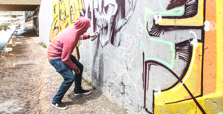 Street artist painting colorful graffiti on public wall - Modern art concept with urban guy performing and preparing live murales with multi color aerosol spray - Bright retro vintage filter