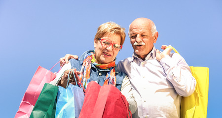 Foto per Senior couple shopping together with wife watching in husband bags - Elderly concept with mature man and woman having fun on sunny day - Happy retired people moments on vivid filter against blue sky - Immagine Royalty Free