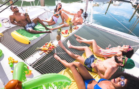 Photo pour Multiracial happy friends having relax fun at sail boat party - Friendship concept with multi racial people on catamaran sailboat - Luxury travel and exclusive vacation concept - Vivid bright filter - image libre de droit
