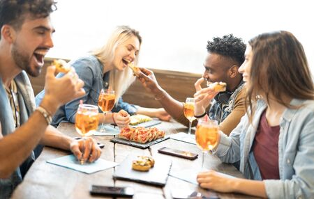 Photo pour Friends eating and drinking spritz at fashion cocktail bar restaurant - Friendship concept with young people having fun together with drinks and food on happy hour at pub - Focus on pizza slices - image libre de droit