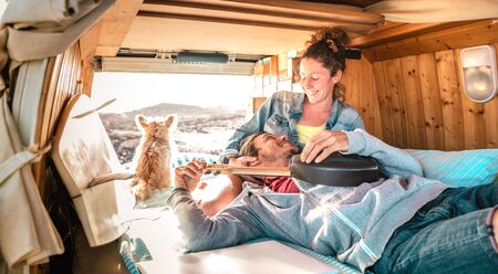 Hippie couple amd dog traveling together on vintage van transport at sunset - Life inspiration concept with guy and girl on minivan adventure trip with ukulele in relax moment - Warm sunshine filter