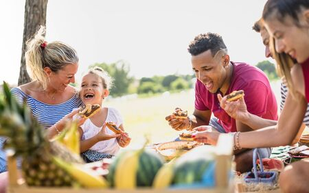 Photo pour Cropped view of happy multiracial families having fun with kids at pic nic barbecue party - Multiethnic love concept with mixed race people eating with children at public park - Warm vivid filter - image libre de droit