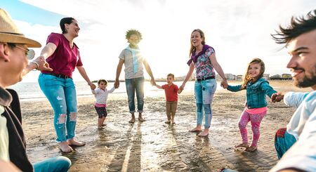 Foto de View point of young families dancing at beach on ring around the rosy style - Lifestyle joy concept with mixed race people having fun moment holding hands - Vivid backlight filter with sunshine halo - Imagen libre de derechos
