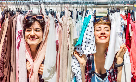 Photo pour Happy women at weekly flea market - Female friends having fun together shopping cloth on sunny day - Millenial lifestyle concept with girlfriends enjoying everyday life moments - Bright vivid filter - image libre de droit